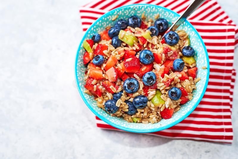 healthy oatmeal with fruits and berries, strawberries, blueberries and figs in a blue bowl on a gray background, for Breakfast. stock photography