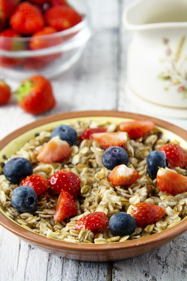 Healthy Homemade Oatmeal with Berries - fresh strwberries and blueberries, for Breakfast. Rustic white wooden table royalty free stock images