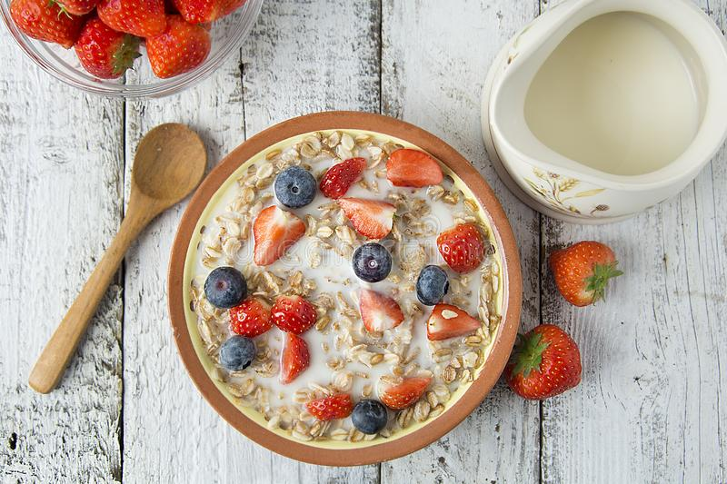 Healthy Homemade Oatmeal with Berries - fresh strwberries and blueberries, for Breakfast. Rustic white wooden table stock photo