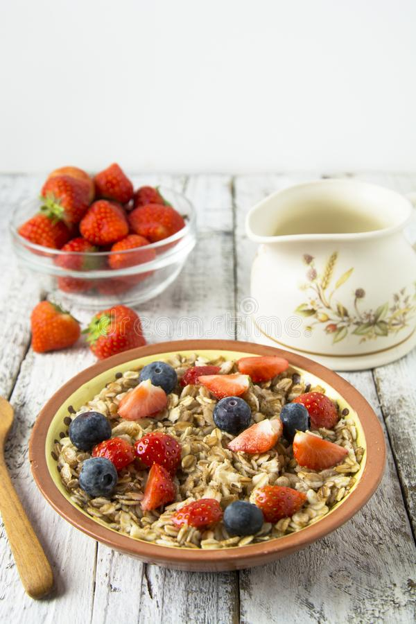 Healthy Homemade Oatmeal with Berries - fresh strwberries and blueberries, for Breakfast. Rustic white wooden table royalty free stock photos