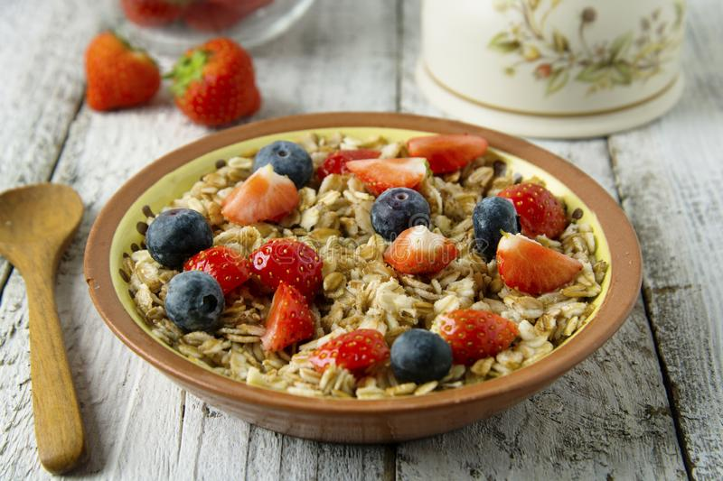 Healthy Homemade Oatmeal with Berries - fresh strwberries and blueberries, for Breakfast. Rustic white wooden table stock image