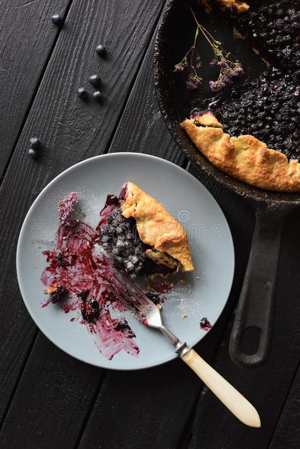 Healthy homemade pastry. Delicious crusty blueberry galette being eaten on black background stock image