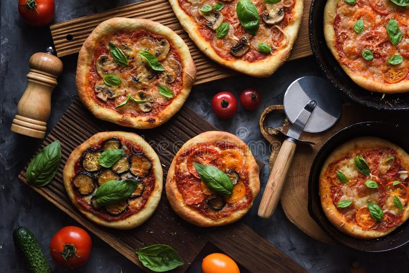 Healthy homemade vegetarian food. Flatlay of rustic freshly baked pizzas with tomatoes, mushrooms, aubergines and basil with pizza stock images