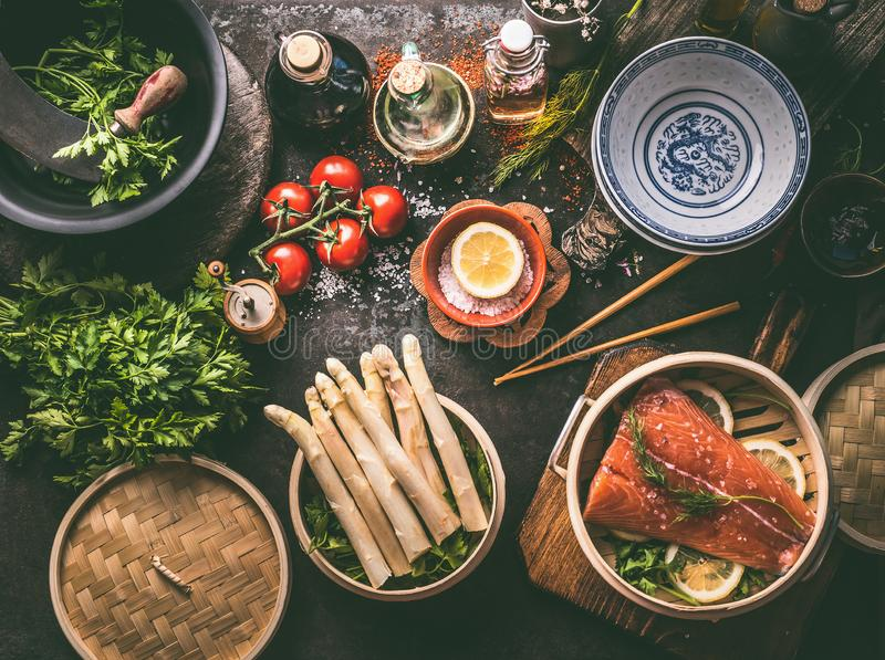 Healthy ingredients for low carb meal cooking: salmon in asian bamboo steamer , asparagus bunch, fresh herbs and oil and sauce. Bottles on dark table background stock photo