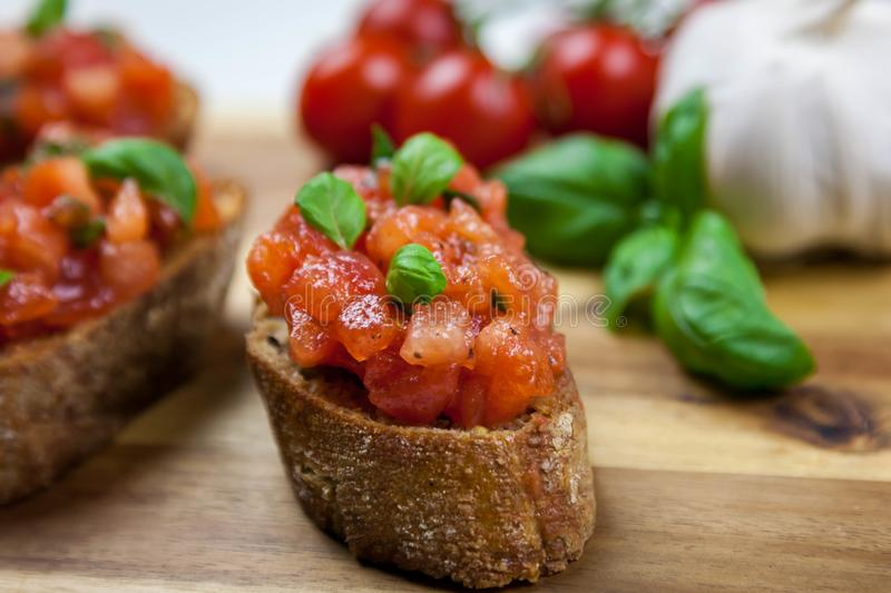 Healthy italian food - bruschetta. Homemade Italian bruschetta appetizer - healthy food, toast with tomatoes, oliven oil and basil royalty free stock photo