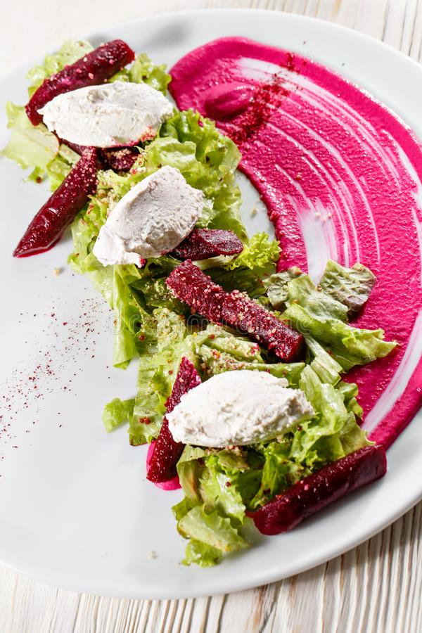 Healthy italian salad with beetroot, lettuce leaves and cheese feta and dressing with oil and mustard seeds. stock photo