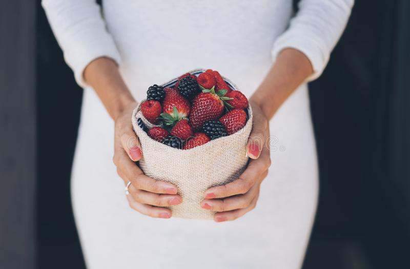 Healthy and juicy berries fruits in woman`s hands with white dress royalty free stock images