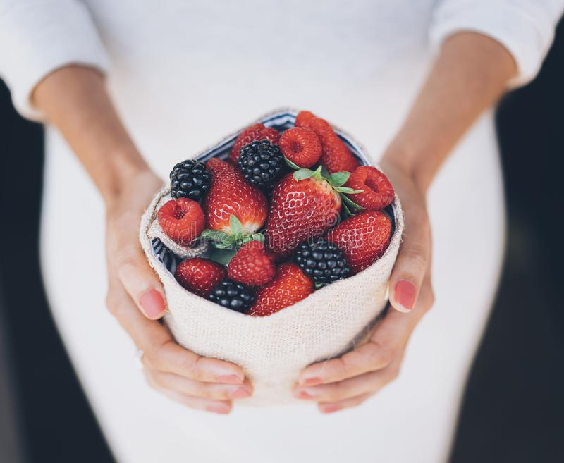 Healthy and juicy berries fruits in woman`s hands with white dress royalty free stock photo