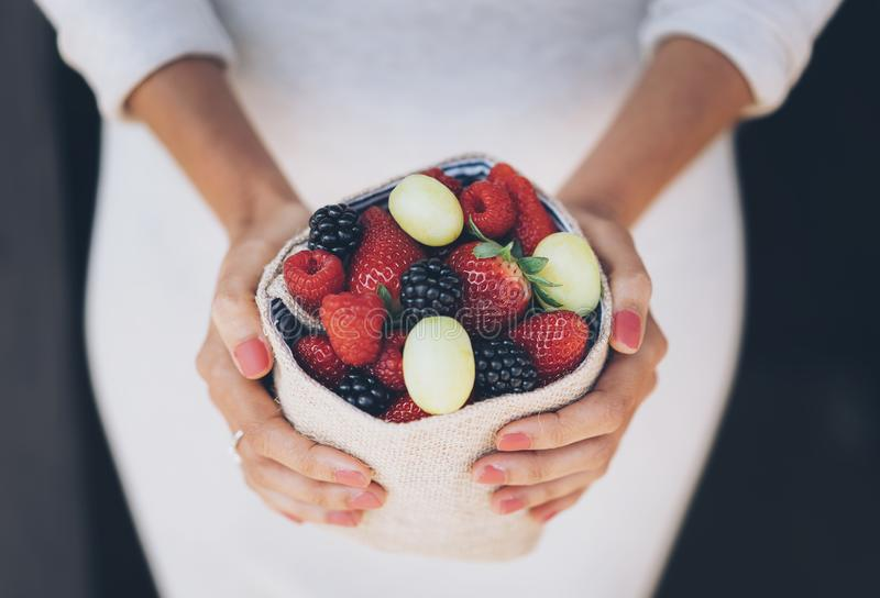 Healthy and juicy berries fruits in woman`s hands with white dress royalty free stock photos