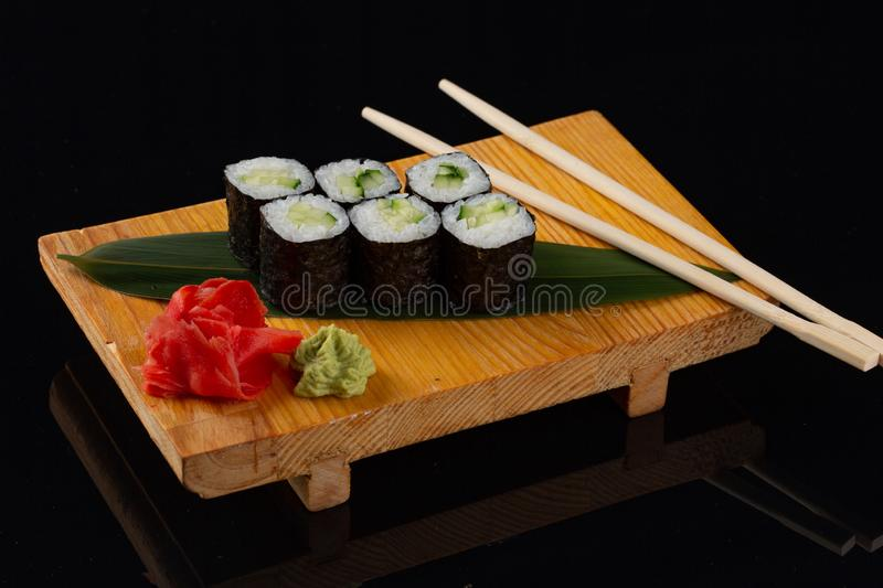 Healthy kale, avocado and cucumber sushi roll on slate serving tray royalty free stock images