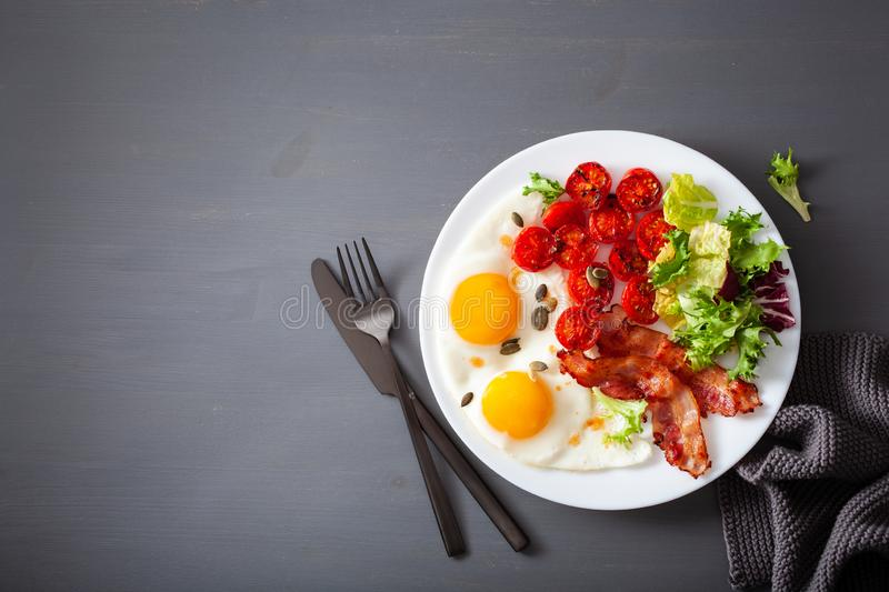 Healthy keto diet breakfast: egg, tomatoes, salad leaves and bacon royalty free stock images
