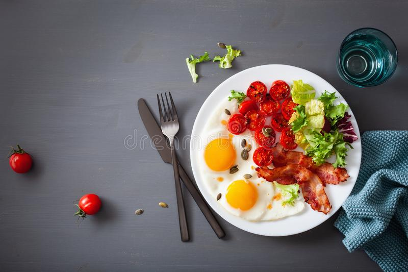 Healthy keto diet breakfast: egg, tomatoes, salad leaves and bacon stock image