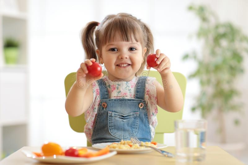 Healthy kids nutrition concept. Cheerful toddler girl sitting at table with plate of salad, vegetables, pasta in room royalty free stock photography
