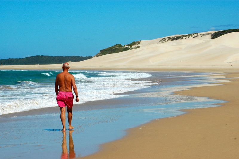 Healthy life. A single elderly caucasian man walking in the water on a lonely beautiful beach by the Indian Ocean in South Africa stock images