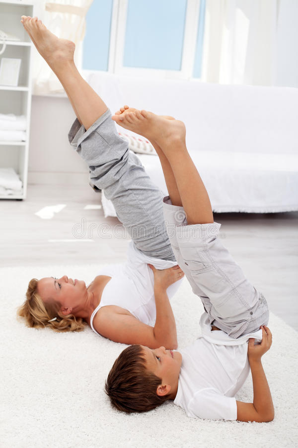 Healthy life education by example. Little boy and his mother exercising at home stock photos