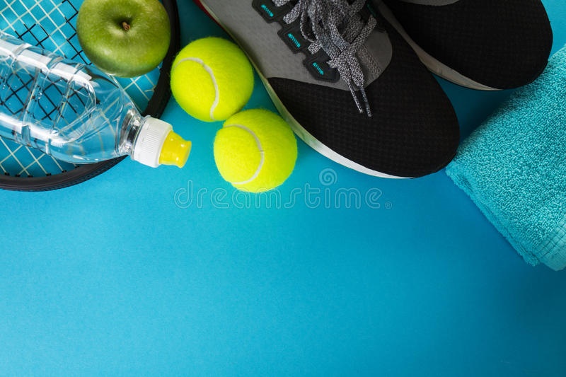 Healthy Life Sport Concept. Sneakers with Tennis Balls, Towel an. D Bottle of Water on Bright Blue Background. Copy Space royalty free stock photo