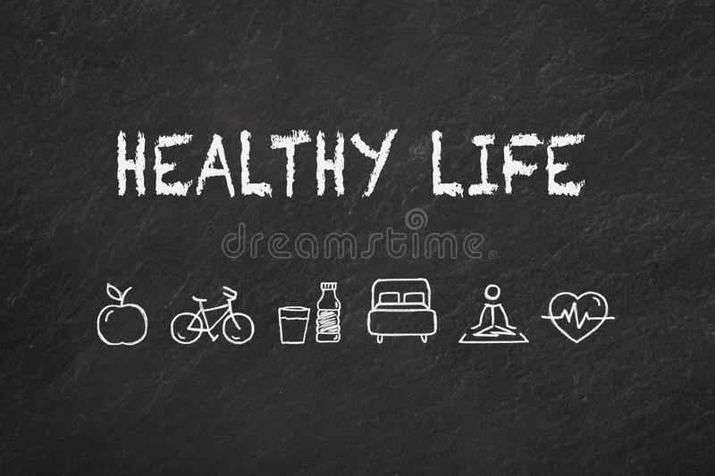 `Healthy life` text and icons on a blackboard. royalty free illustration