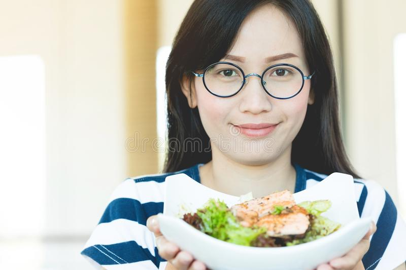 Healthy lifestyle asian woman showing salad smiling. stock image