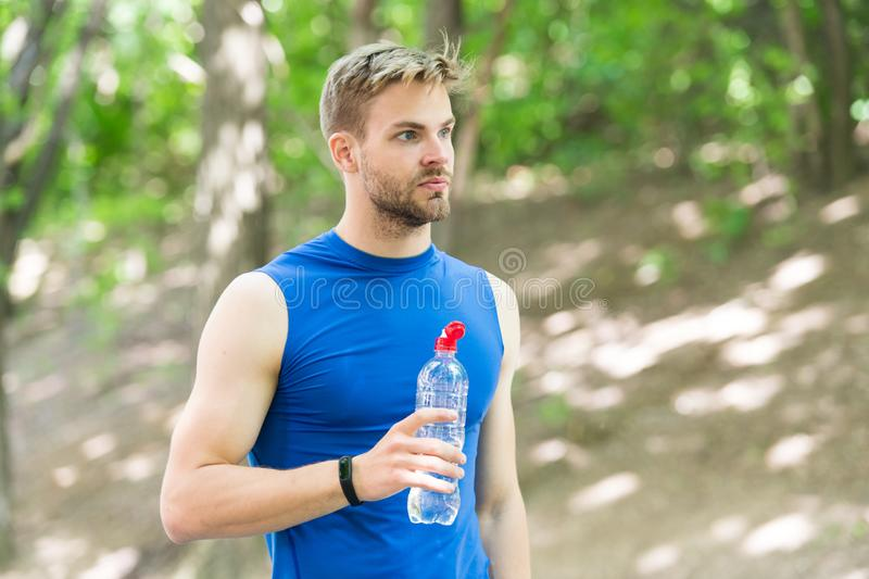 Healthy lifestyle. Athlete drink water after training in park. Vitamins and minerals. Refreshing drink. Man athletic. Sportsman hold bottle water. Man athlete stock images