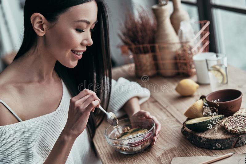 Healthy lifestyle. Attractive young woman eating healthy breakfast and smiling while sitting near the window at home stock photography