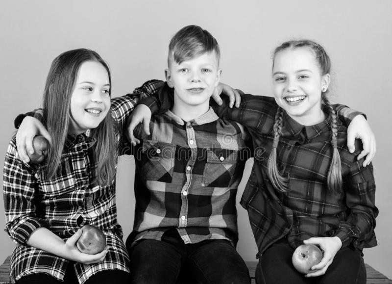 Healthy lifestyle. Boy and girls friends in similar checkered clothes eat apple. Teens with healthy snack. Healthy royalty free stock images