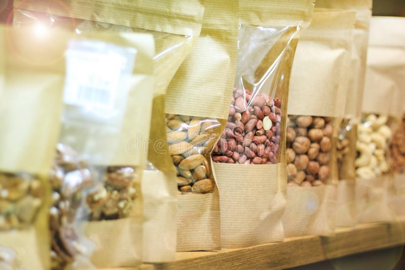 Healthy lifestyle, clean and natural food. Nuts - raisins, peanuts, hazelnuts. packed in paper bags, stand on the counter in the s stock photo