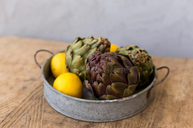 Healthy lifestyle concept. Artichokes and lemons in round metal. Tray on wooden tabletop against blurred gray wall. Horizontal composition stock image
