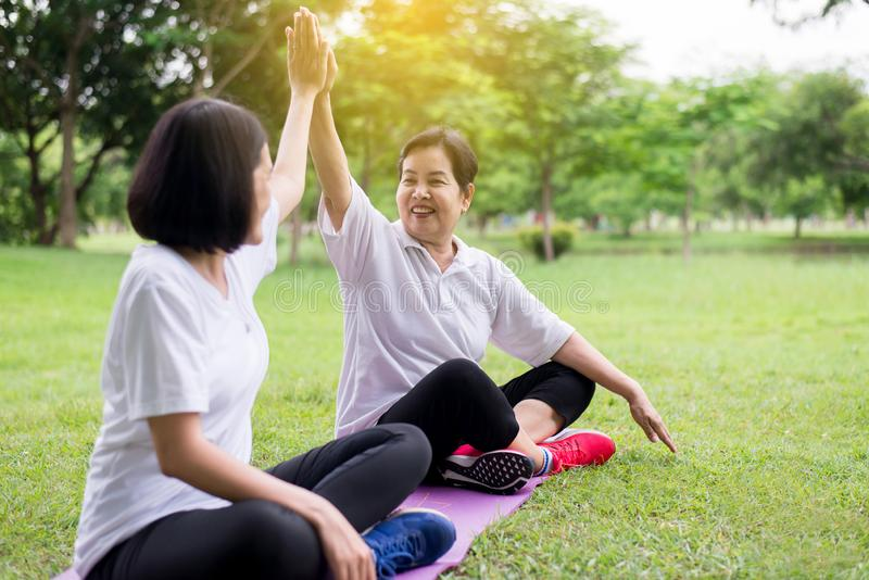 Healthy and lifestyle concept,Asian women raise up hands and relax at park in the morning together,Happy and smiling,Positive thin. King royalty free stock photos