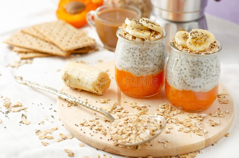 Healthy lifestyle concept. Breakfast with coffee, crackers, oat flakes, chia seed pudding with banana and apricot stock photos