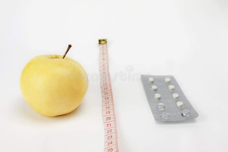 Healthy lifestyle concept. The choice between correct nutrition and permanent treatment. Apple with medical drugs divided by royalty free stock images