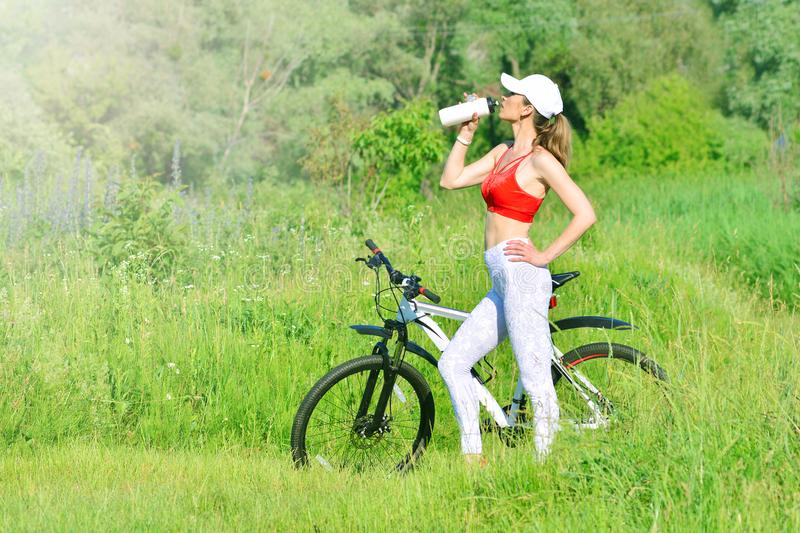 Healthy lifestyle concept. Fitness girl rests near the bicycle outdoors and drinks water from bottle. Burning calories concept royalty free stock photography