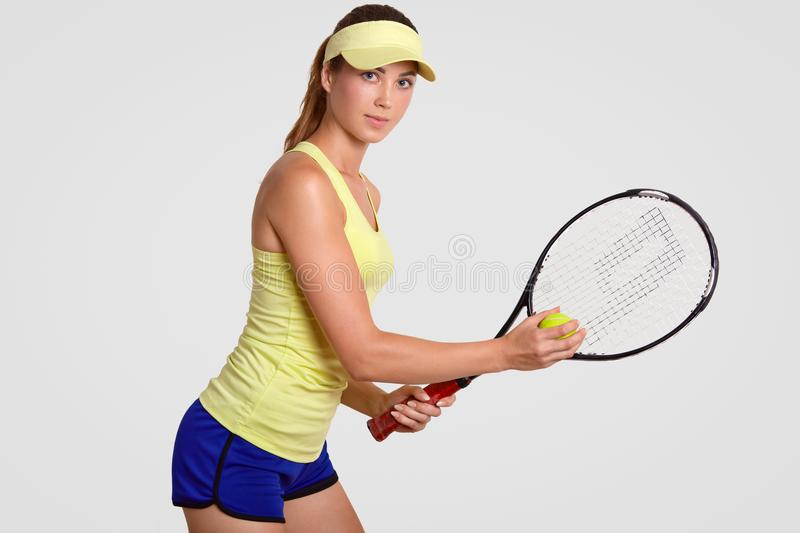 Healthy lifestyle concept. Motivated active experienced lovely female tennis player, ready to make short ball, holds tennis racque royalty free stock image