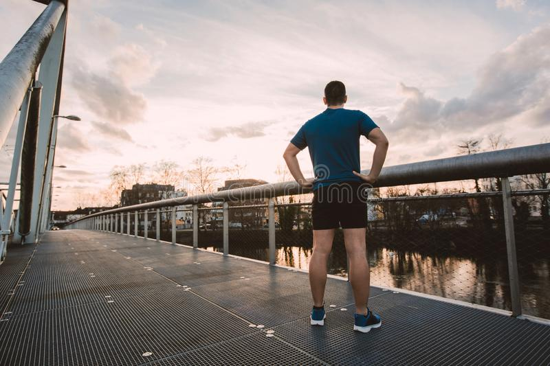Healthy lifestyle concept. Rear view athlete man relaxing after a long run watching sunset over city. Recreational activities concept.Self overcome concept royalty free stock image