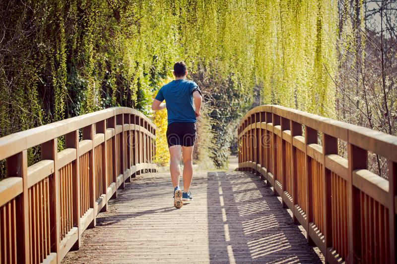 Healthy lifestyle concept. Rear view Male runner running in a city park over  bridge training for fitness. Healthy lifestyle concept. Workout jogging activity royalty free stock photos