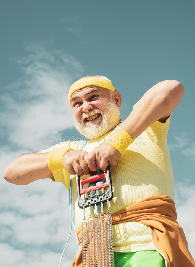 Healthy lifestyle concept. Senior man in health club. Senior man exercising on blue sky. Senior sport man is doing sport. Outdoors. Grandfather sportsman on stock photography