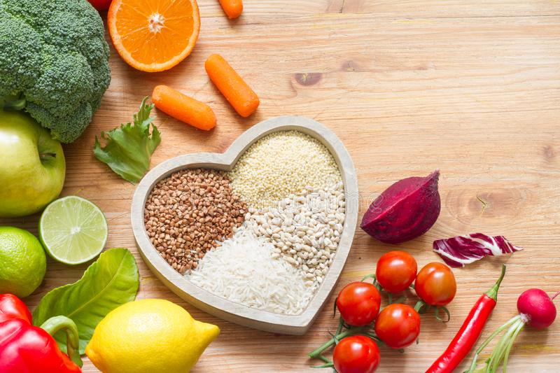 Healthy lifestyle concept with vegetarian food in heart diet background. On wooden board stock photos