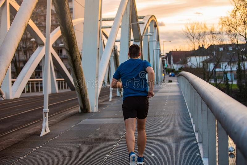 Healthy lifestyle concept. Workout jogging activity. Young athletic man practicing sport outdoors, running fast along bridge over the sunset sky background. Self royalty free stock image