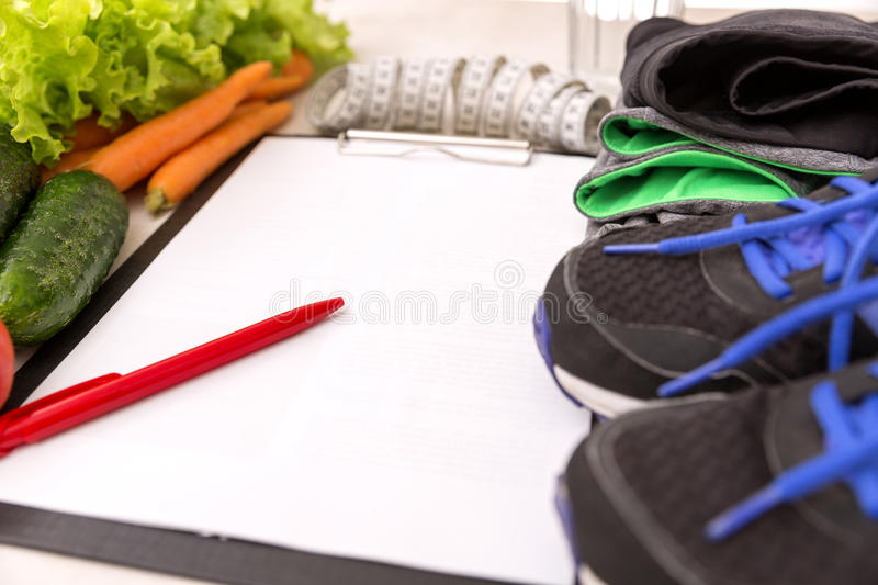 Healthy lifestyle concept. Writing weight loss plan with fresh vegetable diet and fitness stock photo