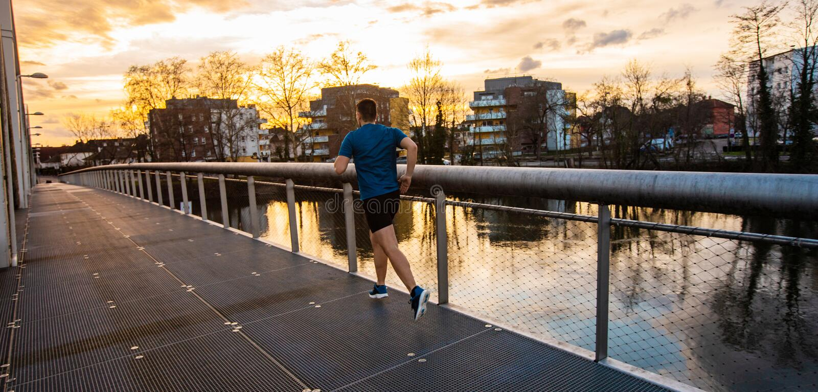 Healthy lifestyle concept. Young athletic man practicing sport outdoors, running fast along bridge over the sunset sky background. Self overcome conquering stock photos