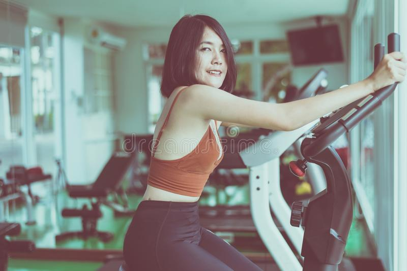 Healthy lifestyle concept,Young teen woman workout with cycling doing cardio training indoor center,Happy and smiling,Close up stock photo