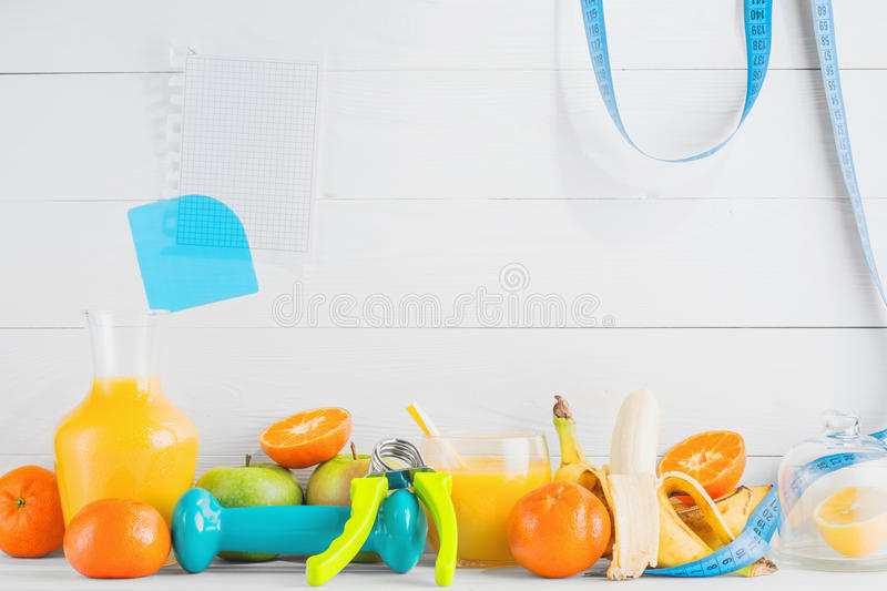 Healthy lifestyle, diet concept. Fruit and juice, orange, tangerine, apple, banana, dumbbell, hand gripper and a blank sheet on white wooden background with stock photo