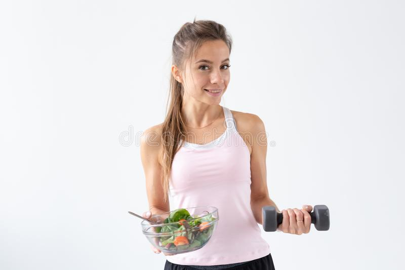 Healthy lifestyle, diet, fitness and people concept - young woman is eating a salad and doing sport with dumbbell on stock photography
