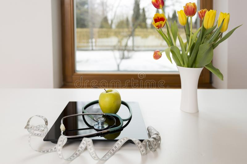 Healthy lifestyle, dieting and nutrition concept. Geen apple on scales next to the measuring tape and stethoscope. Spring dieting.  royalty free stock photo