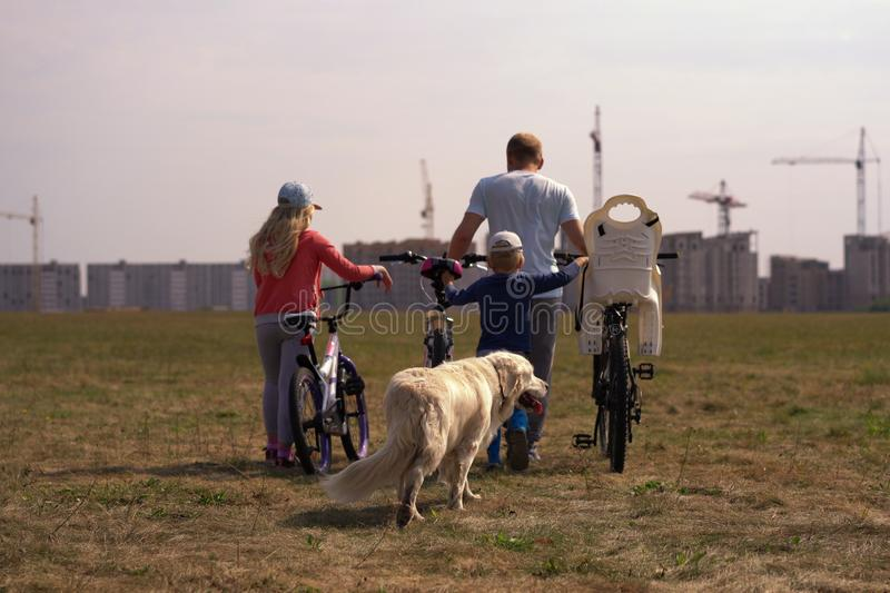 Healthy lifestyle - family with bicycles and a dog walking along the field near the city stock photos