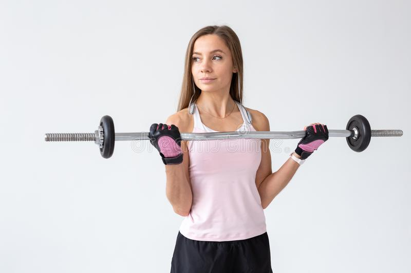 Healthy lifestyle, fitness, people and sport concept - Young woman workout with body bar over white background.  stock image