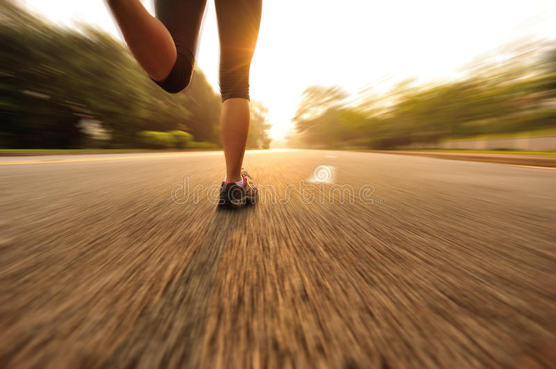 Healthy lifestyle fitness sports woman running leg. Healthy lifestyle fitness sports woman legs running at sunrise road royalty free stock photos