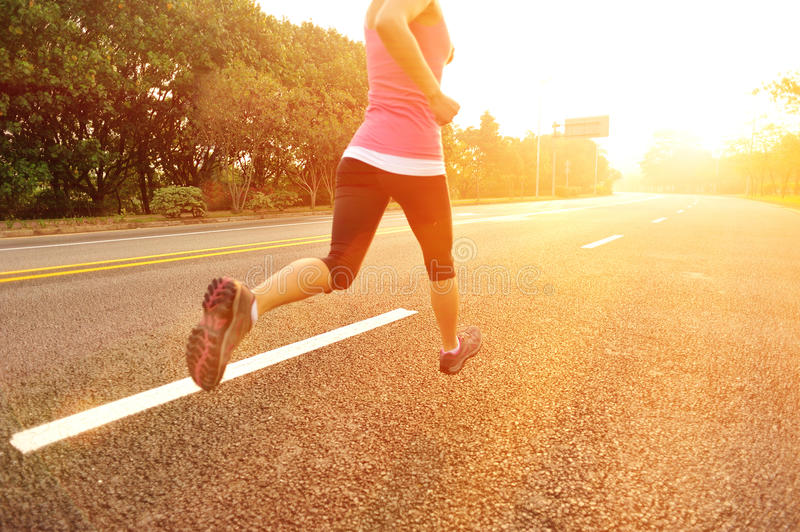 Healthy lifestyle fitness sports woman running. At sunrise road stock photography