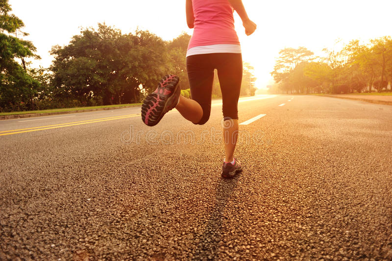 Healthy lifestyle fitness sports woman running. At sunrise road stock image