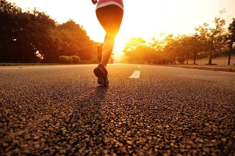 Healthy lifestyle fitness sports woman running. At sunrise road stock photo