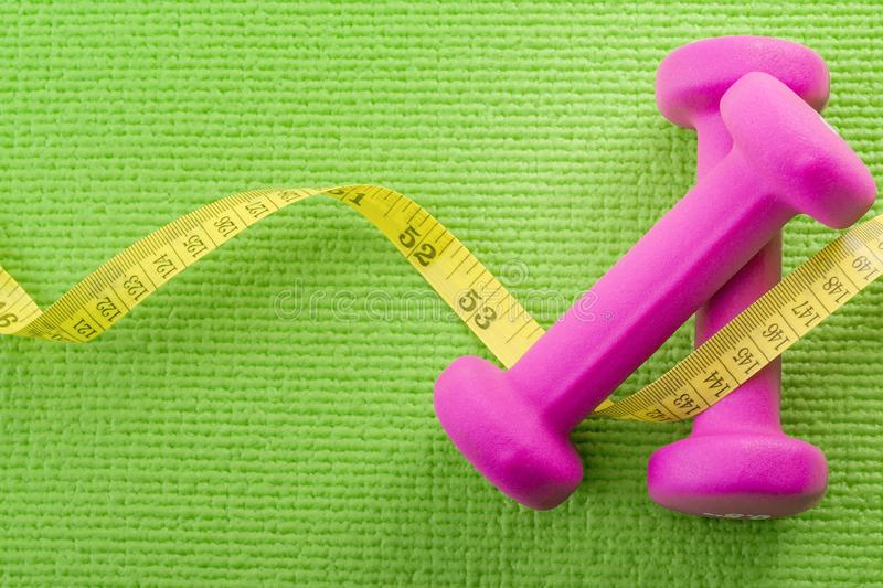 Healthy lifestyle, fitness and weight control concept with a closeup pink on a pair dumbbells with measuring tape wrapped around stock photo